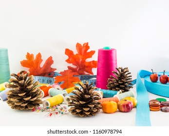 Sewing fall image. An autumn feeling with pine cones, fall leaves, pumkins and mini apples. Sewing items like colorful threads, buttons, straight pins and a tape measure on a white background..