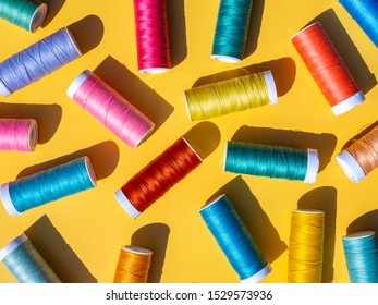 Sewing flat lay. Colorful spools of thread on a yellow background. Bright sunny day, shadows.