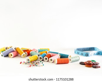 Sewing image with colorful sewing notions. Thread bobbins, tape measure, buttons and straight pins on a white background. Front view with copy space.