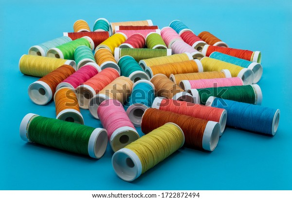 Sewing image with many colorful spools of thread on a blue background.
