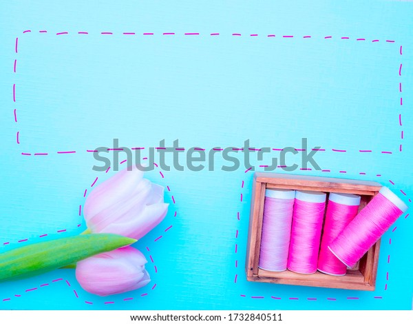 Sewing image with pink sewing threads and a pink tulip on a blue background. Sewing stitches drawn around the items. Room for copy.