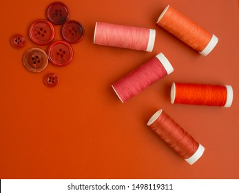 Sewing image with red sewing notions. Red bobbins and red vintage buttons on a red background. Top view. Room for text.