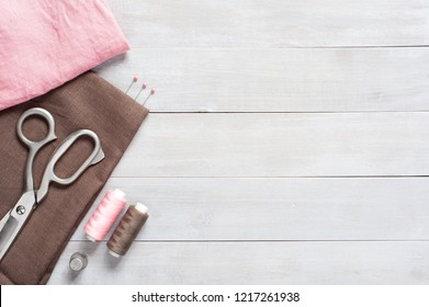 Sewing items and linen fabric on the light wooden table, wooden background
