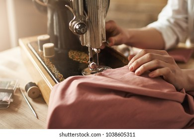 Sewing keeps my mind relaxed. Cropped shot of female tailor working on new project, making clothes with sewing machine in workshop, being busy. Young designer making her ideas come true