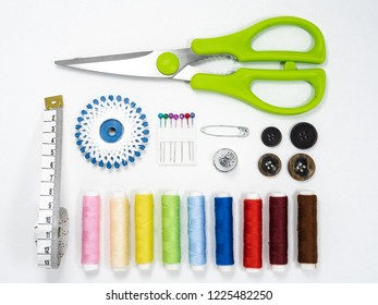 Sewing kit with color threads, scissors, measuring tape and some buttons, arranged on white surface background and viewed from above