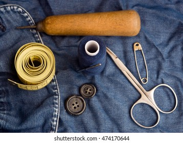 sewing kit on denim.  thread, needles, scissors, measuring ruler, pins, buttons, sewed