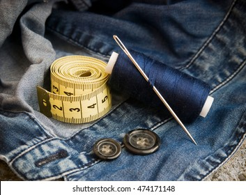 sewing kit on denim.  thread, needle, measuring ruler, buttons,