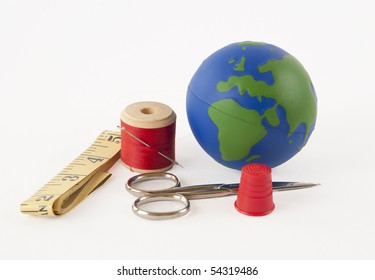 Sewing kit with a small globe representing the concept of mending the planet