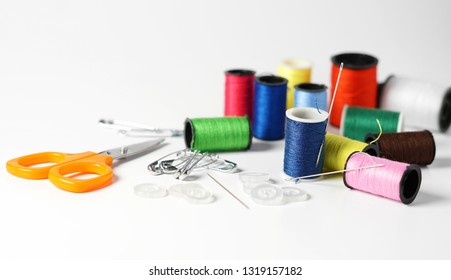 Sewing kit for tailoring with colorful cotton threads of different sizes, needle, scissor and buttons close up view on white background.