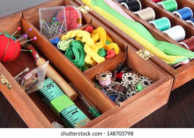 Sewing kit in wooden box on wooden table