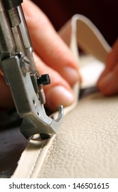 sewing machine in action for working leather for a sofa