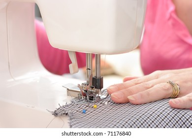 Sewing machine being used with selective focus on pressure foot and needle