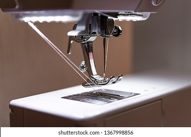 Sewing machine close-up: presser foot, needle, feed dog