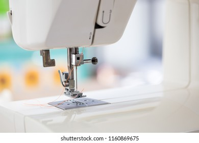 sewing machine with colour thread and needle on a table with blurred background, Tailor's work table, textile or fine cloth making, industrial fabric, home appliances tool.