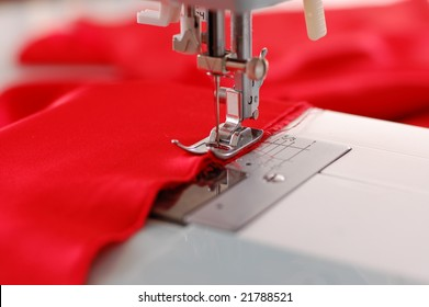 Sewing machine detail with the red thread and cloth