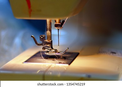Sewing machine with fabric and thread. Work by the light of the built-in hardware lamp. Steel needle with looper and presser foot close-up.