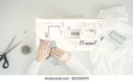 Sewing machine on table, top view shot. Female hands on table with scissors, material, spool of thread and sewing machine. Studio atelier bright white shot
