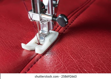 sewing machine and red leather with a seam close-up. sewing process.