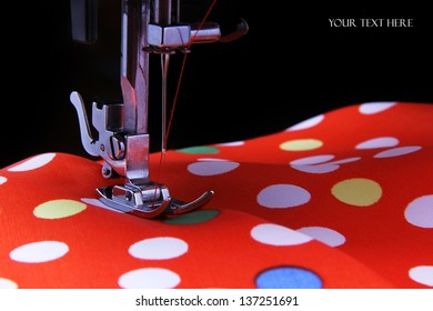 Sewing machine in the studio scribbling a red fabric with polka dots