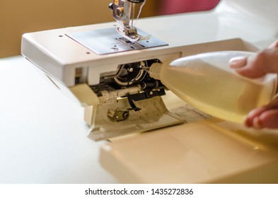 Sewing machine. Work in the light built into the hardware lamp. Steel needle with looper and leg close up. Preparation for work, the seamstress serves the sewing machine after work.