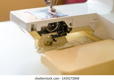 Sewing machine. Work in the light built into the hardware lamp. Steel needle with looper and leg close up. Preparation for work, the seamstress changes the hook with the bottom thread.