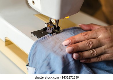 Sewing machine. Work in the light of the built-in hardware lamp. Steel needle with looper and foot close-up. Seamstress sews clothes made of blue cloth on a sewing machine.