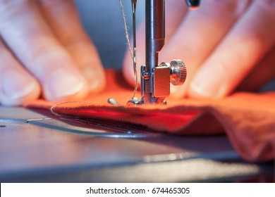 Sewing machine's foot on a red fabric a background of women's hands (out of focus)