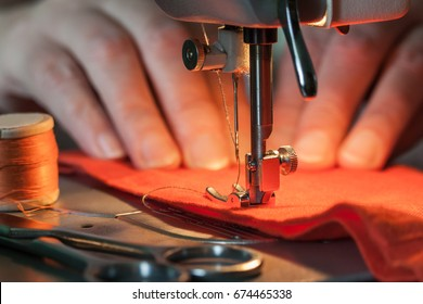 Sewing machine's foot on a red fabric a background of women's hands (out of focus), Near lies skein of threads and scissors
