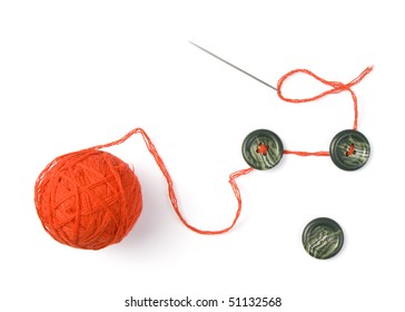 Sewing needle with red ball of threads and buttons