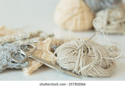 Sewing needle threaded with hemp, yarn, crochet, and scissors in neutral colors
