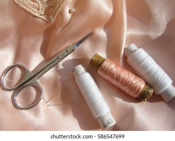 Sewing and Needlework: thread, needles, lace, ribbon, scissors, cloth.