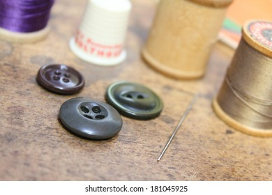 Sewing notions, buttons needle and thread on rustic wood background