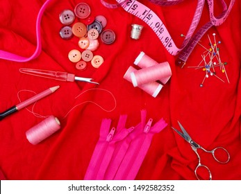 Sewing notions flat lay in red. Red fabric, red buttons, pink sewing thread, scissors, tape measure, tailors chalk, buttons, straight pins, zippers, seam ripper and a thimble. Top view.