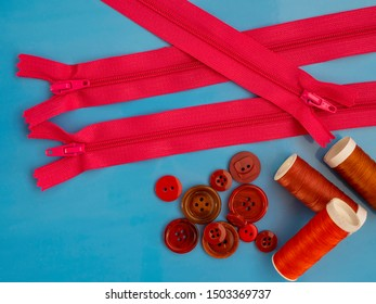 Sewing notions in red. Zippers, buttons and sewing threads. On a blue background. Top view.
