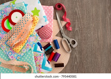 Sewing and objects for sewing. View from above. Fabric, tailoring scissors, centimeter tape, thread, ribbon, drawings are needed for sewing clothes. Sewing items are stacked together.