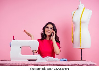 sewing pattern,sewing machine and maniken in studio pink background.seamstress curve template. tailor creates a collection outfits sews clothes in workshop. young woman designer clothes notes ideas