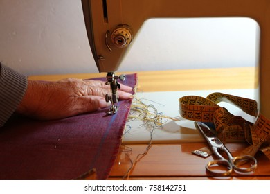 sewing pink cloth on sewing machine. scissors and sewing meter. old hand