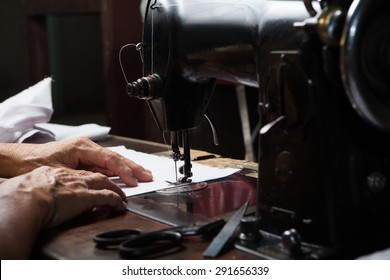 Sewing Process, Antique Sewing Machine with sewer, Lowkey lighting, Focus at needle