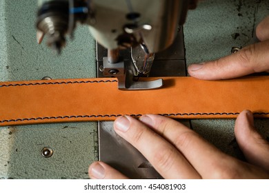 Sewing process of the leather belt. Man's hands behind sewing. Leather workshop.