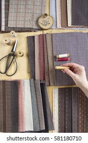 Sewing process with woman's hands on the background with vintage scissors, pins, fabrics in pastel colors and spools.