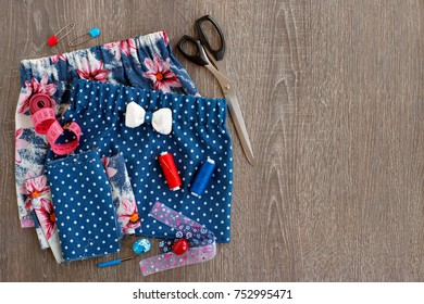 Sewing a skirt on an elastic band. Sew a skirt with a bow for the girl. Scissors, fabric, centimeter tape, thread reels are needed for sewing clothes. Skirt on an elastic band and tailoring.