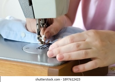 Sewing striped shirt on a sewing machine. Сlose up