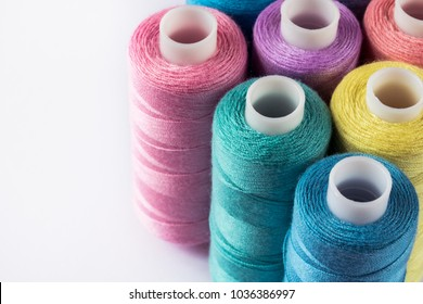 Sewing supplies and accessories for needlework. coils of yellow pink green thread for sewing clothes on white background.