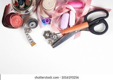 Sewing supplies and accessories for needlework. Scissors, threads, needles, tapes, buttons, tape measure, thimble, seam ripper, fabric on white table background. Top view, copy space