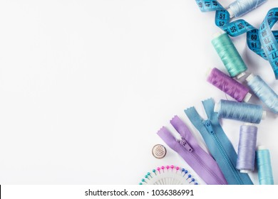 Sewing supplies and accessories for needlework. Spools of thread and other equipment blue violet colour that uses a tailor to sew clothes on white background.