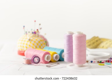 Sewing supplies on a white wooden table: sewing thread, scissors, a large spool of thread, pieces of cloth, needles,centimeter, buttons