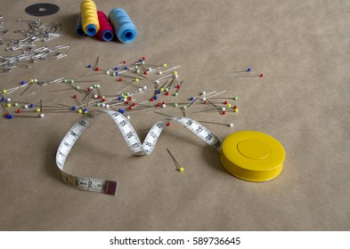 Sewing supplies such as pins, colorful spools, scissors. On the craft paper covered table.