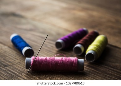 a sewing thread on a wooden background