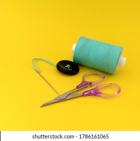 Sewing threads spool with sewing needle isolated on yellow background