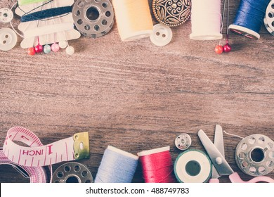 Sewing tools and kit on a wooden background in vintage style color